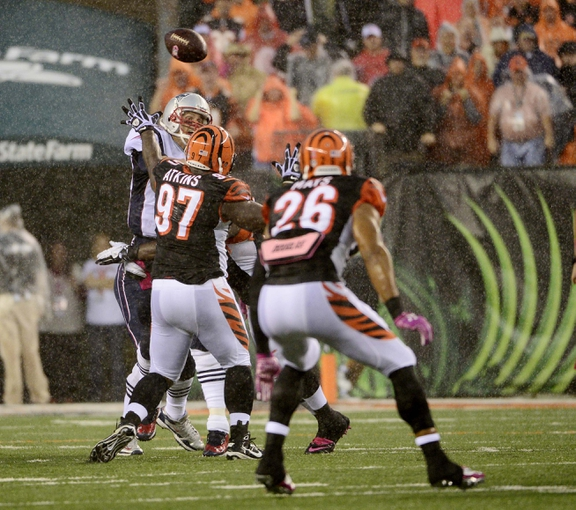 Oct 6, 2013; Cincinnati, OH, USA; New England Patriots quarterback Tom Brady (12)  gets a pass by Cincinnati Bengals defensive tackle Geno Atkins (97) at Paul Brown Stadium. The Bengals won 13-6.  Mandatory Credit: Marc Lebryk-USA TODAY Sports