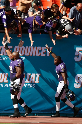 Oct 6, 2013; Miami Gardens, FL, USA; Baltimore Ravens defensive tackle Brandon Williams (98) and  defensive back Anthony Levine (41) celebrate the Ravens win over the Miami Dolphins 26-23 at Sun Life Stadium. Mandatory Credit: Robert Mayer-USA TODAY Sports