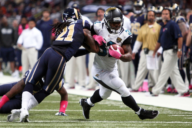Oct 6, 2013; St. Louis, MO, USA; Jacksonville Jaguars running back Maurice Jones-Drew (32) takes a hit from St. Louis Rams cornerback Janoris Jenkins (21) as he carries the ball during the second half at The Edward Jones Dome. Mandatory Credit: Scott Kane-USA TODAY Sports