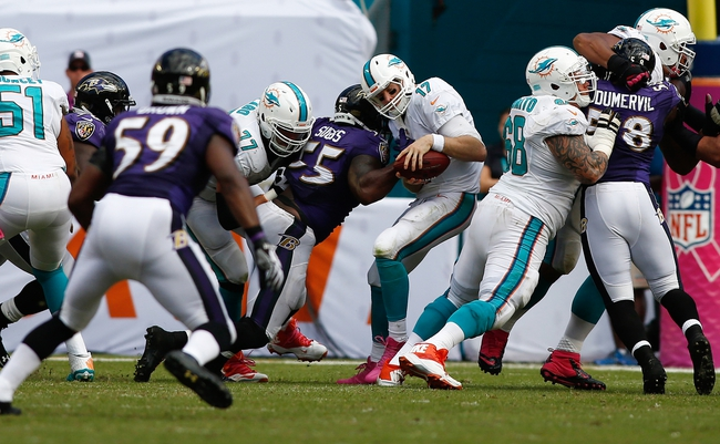 Oct 6, 2013; Miami Gardens, FL, USA; Miami Dolphins quarterback Ryan Tannehill (17) is sacked by Baltimore Ravens outside linebacker Terrell Suggs (55) in the second half at Sun Life Stadium. Mandatory Credit: Robert Mayer-USA TODAY Sports