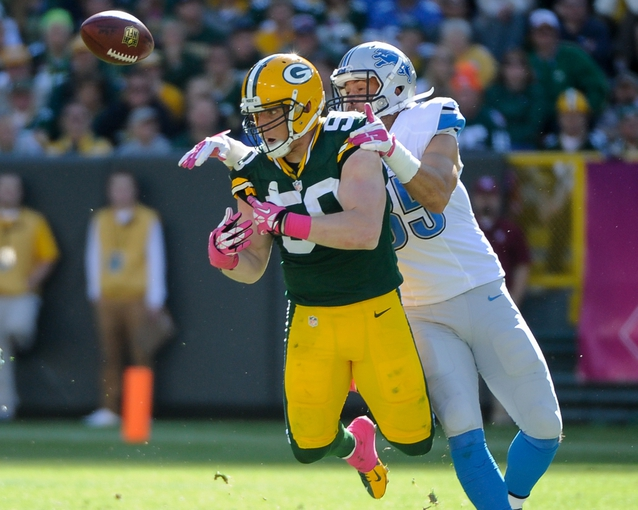 Oct 6, 2013; Green Bay, WI, USA; Green Bay Packers linebacker A.J. Hawk (50) breaks up a pass intended for Detroit Lions tight end Tony Scheffler (85) in the fourth quarter at Lambeau Field. Mandatory Credit: Benny Sieu-USA TODAY Sports
