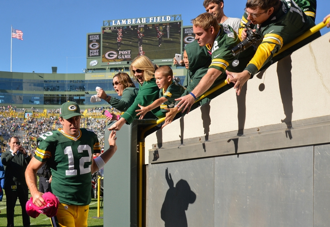 Oct 6, 2013; Green Bay, WI, USA; Green Bay Packers quarterback Aaron Rodgers (12) is greeted by fans after defeating the Detroit Lions 22-9 at Lambeau Field. Mandatory Credit: Benny Sieu-USA TODAY Sports