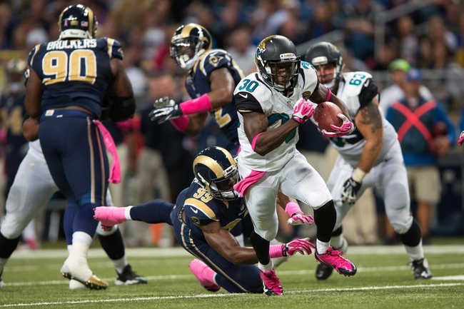 Oct 6, 2013; St. Louis, MO, USA; Jacksonville Jaguars running back Jordan Todman (30) carries the ball as St. Louis Rams defensive end Gerald Rivers (99) defends during the second half at the Edward Jones Dome. St. Louis defeated Jacksonville 34-20. Mandatory Credit: Jeff Curry-USA TODAY Sports