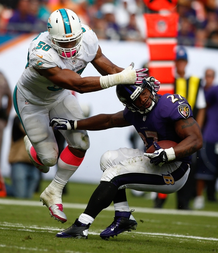 Oct 6, 2013; Miami Gardens, FL, USA; Miami Dolphins defensive end Olivier Vernon (50) tackles Baltimore Ravens running back Ray Rice (27) in the second half at Sun Life Stadium. Mandatory Credit: Robert Mayer-USA TODAY Sports