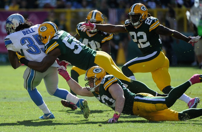 Oct 6, 2013; Green Bay, WI, USA; Green Bay Packers linebacker A.J. Hawk (50) and linebacker Andy Mulumba (55) tackle Detroit Lions running back Joique Bell (35) in the fourth quarter at Lambeau Field. The Packers won 22-9. Mandatory Credit: Benny Sieu-USA TODAY Sports