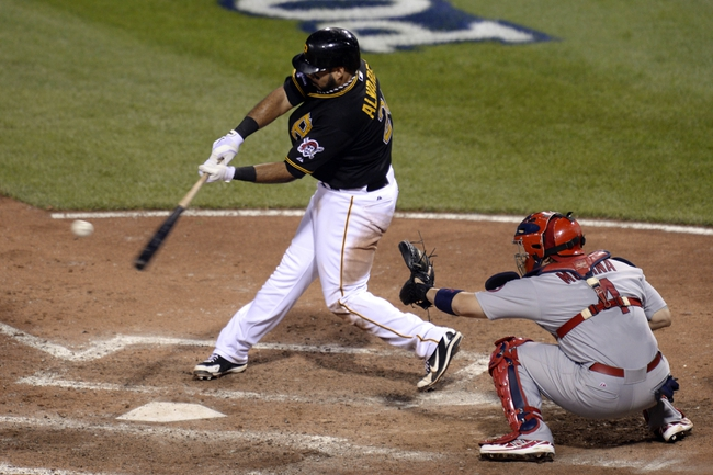 Oct 6, 2013; Pittsburgh, PA, USA; Pittsburgh Pirates third baseman Pedro Alvarez (24) hits a RBI single against the St. Louis Cardinals during the 8th inning in game three of the National League divisional series playoff baseball game at PNC Park. Mandatory Credit: H.Darr Beiser-USA TODAY Sports