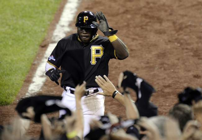 Oct 6, 2013; Pittsburgh, PA, USA; Pittsburgh Pirates pinch runner Josh Harrison is congratulated by teammates after scoring a run against the St. Louis Cardinals during the 8th inning in game three of the National League divisional series playoff baseball game at PNC Park. Mandatory Credit: H.Darr Beiser-USA TODAY Sports