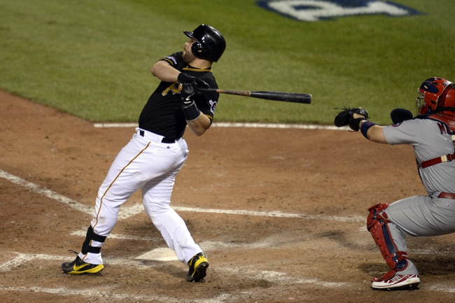 Oct 6, 2013; Pittsburgh, PA, USA; Pittsburgh Pirates catcher Russell Martin hits a RBI single against the St. Louis Cardinals during the 8th inning in game three of the National League divisional series playoff baseball game at PNC Park. Mandatory Credit: H.Darr Beiser-USA TODAY Sports