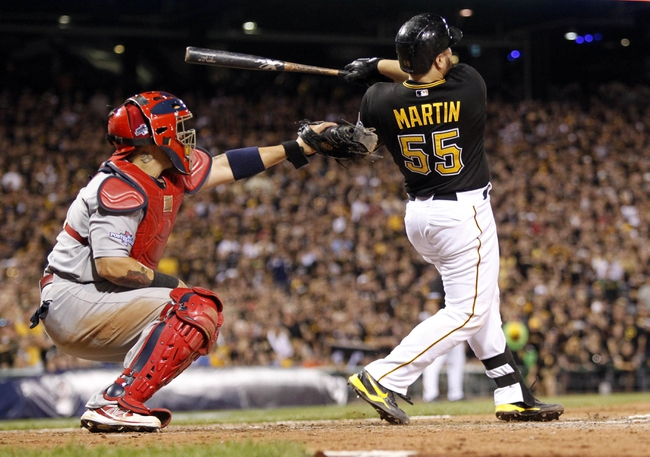 Oct 6, 2013; Pittsburgh, PA, USA; Pittsburgh Pirates catcher Russell Martin (55) hits a RBI single against the St. Louis Cardinals in the 8th inning in game three of the National League divisional series playoff baseball game at PNC Park. Mandatory Credit: Charles LeClaire-USA TODAY Sports