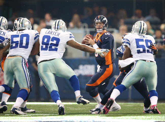 Oct 6, 2013; Arlington, TX, USA; Denver Broncos quarterback Peyton Manning (18) throws in the pocket under pressure from Dallas Cowboys defensive tackle David Carter (92) in the third quarter at AT&T Stadium.  The Denver Broncos beat the Dallas Cowboys 51-48.  Mandatory Credit: Matthew Emmons-USA TODAY Sports