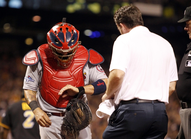 Oct 6, 2013; Pittsburgh, PA, USA; St. Louis Cardinals catcher Yadier Molina (left) reacts after an apparent hand injury as a trainer arrivesduring the eighth inning in game three of the National League divisional series playoff baseball game against the Pittsburgh Pirates at PNC Park. Pittsburgh won 5-3. Mandatory Credit: Charles LeClaire-USA TODAY Sports