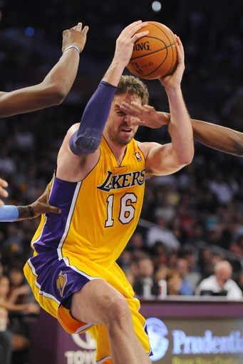Oct 6, 2013; Los Angeles, CA, USA; Los Angeles Lakers forward Pau Gasol (16) is hit while driving to the basket during the first half against the Denver Nuggets at Staples Center. Mandatory Credit: Christopher Hanewinckel-USA TODAY Sports