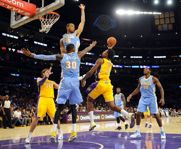 Oct 6, 2013; Los Angeles, CA, USA; Los Angeles Lakers guard Nick Young (0) attempts a shot over Denver Nuggets forward Anthony Randolph (15) and forward Quincy Miller (30) during the first half at Staples Center. Mandatory Credit: Christopher Hanewinckel-USA TODAY Sports
