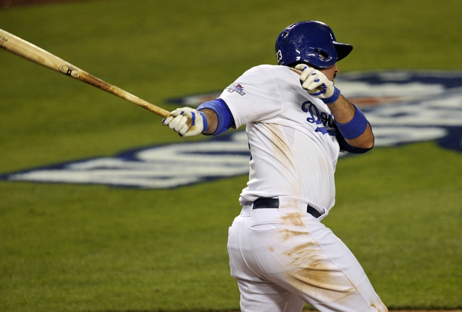 October 6, 2013; Los Angeles, CA, USA; Los Angeles Dodgers first baseman Adrian Gonzalez (23) hits an RBI single in the eighth inning against the Atlanta Braves in game three of the National League divisional series playoff baseball game at Dodger Stadium. Mandatory Credit: Robert Hanashiro-USA TODAY Sports