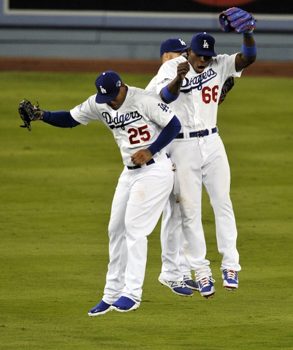 October 6, 2013; Los Angeles, CA, USA; Los Angeles Dodgers left fielder Carl Crawford (25), outfielder Skip Schumaker (55) and right fielder Yasiel Puig (66) celebrate the 13-6 victory against the Atlanta Braves following game three of the National League divisional series playoff baseball game at Dodger Stadium. Mandatory Credit: Robert Hanashiro-USA TODAY Sports