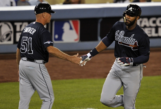 October 6, 2013; Los Angeles, CA, USA; Atlanta Braves right fielder Jason Heyward (22) is congratulated by third base coach Brian Snitker (51) after hitting a two run home run in the ninth inning against the Los Angeles Dodgers in game three of the National League divisional series playoff baseball game at Dodger Stadium. Mandatory Credit: Robert Hanashiro-USA TODAY Sports