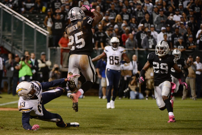 October 6, 2013; Oakland, CA, USA; Oakland Raiders cornerback DJ Hayden (25) intercepts the ball against San Diego Chargers wide receiver Keenan Allen (13) during the fourth quarter at O.co Coliseum. The Raiders defeated the Chargers 27-17. Mandatory Credit: Kyle Terada-USA TODAY Sports