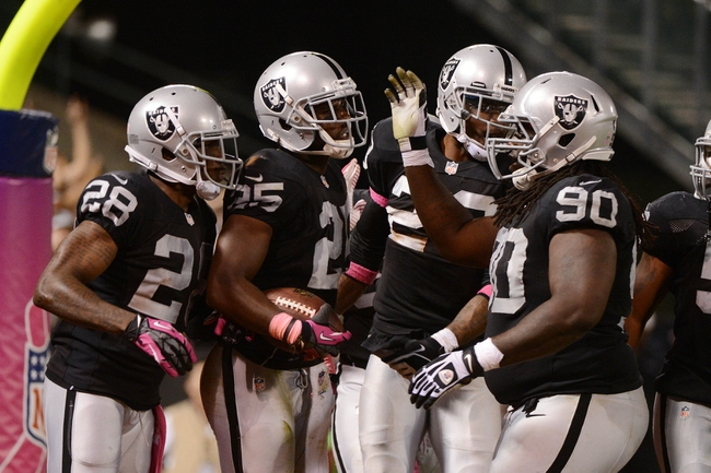 October 6, 2013; Oakland, CA, USA; Oakland Raiders cornerback DJ Hayden (25) is congratulated by cornerback Phillip Adams (28) and defensive tackle Pat Sims (90) for intercepting the ball against the San Diego Chargers during the fourth quarter at O.co Coliseum. The Raiders defeated the Chargers 27-17. Mandatory Credit: Kyle Terada-USA TODAY Sports