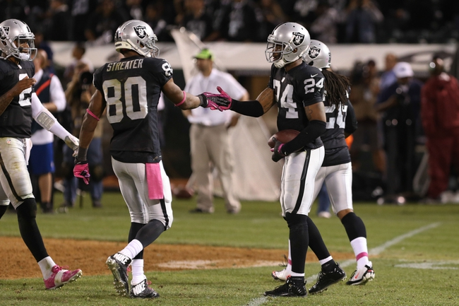 Oct 6, 2013; Oakland, CA, USA; Oakland Raiders free safety Charles Woodson (24) celebrates with wide receiver Rod Streater (80) after intercepting the ball against the San Diego Chargers during the fourth quarter at O.co Coliseum. The Oakland Raiders defeated the San Diego Chargers 27-17. Mandatory Credit: Kelley L Cox-USA TODAY Sports