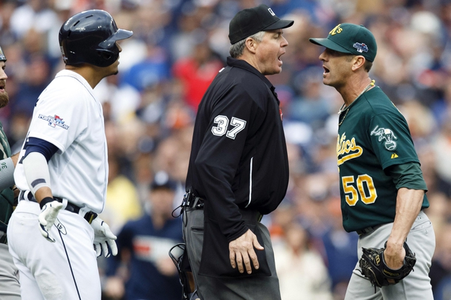 Oct 7, 2013; Detroit, MI, USA; Home plate umpire Gary Darling (37) gets between Detroit Tigers designated hitter Victor Martinez (left) and Oakland Athletics relief pitcher Grant Balfour (50) in the ninth inning in game three of the American League divisional series playoff baseball game at Comerica Park. Oalkand won 6-3. Mandatory Credit: Rick Osentoski-USA TODAY Sports