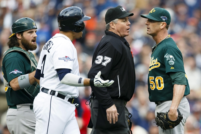 Oct 7, 2013; Detroit, MI, USA; Home plate umpire Gary Darling (37) gets between Detroit Tigers designated hitter Victor Martinez (41) and Oakland Athletics relief pitcher Grant Balfour (50) in the ninth inning in game three of the American League divisional series playoff baseball game at Comerica Park. Oalkand won 6-3. Mandatory Credit: Rick Osentoski-USA TODAY Sports
