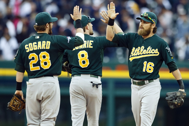 Oct 7, 2013; Detroit, MI, USA; Oakland Athletics second baseman Eric Sogard (28) , shortstop Jed Lowrie (8) and right fielder Josh Reddick (16) celebrate after game three of the American League divisional series playoff baseball game against the Detroit Tigers at Comerica Park. Oakland won 6-3. Mandatory Credit: Rick Osentoski-USA TODAY Sports