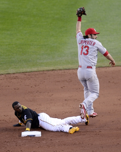Oct 7, 2013; Pittsburgh, PA, USA; Pittsburgh Pirates base runner Josh Harrison (left) reacts after being caught stealing by St. Louis Cardinals second baseman Matt Carpenter (13) in game four of the National League divisional series at PNC Park. Mandatory Credit: H.Darr Beiser-USA TODAY Sports