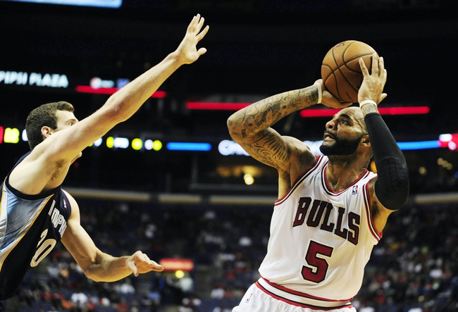 Oct 7, 2013; St. Louis, MO, USA; Chicago Bulls power forward Carlos Boozer (5) puts up a shot as Memphis Grizzlies power forward Jon Leuer (30) defends during the first quarter at Scottrade Center. Mandatory Credit: Jeff Curry-USA TODAY Sports