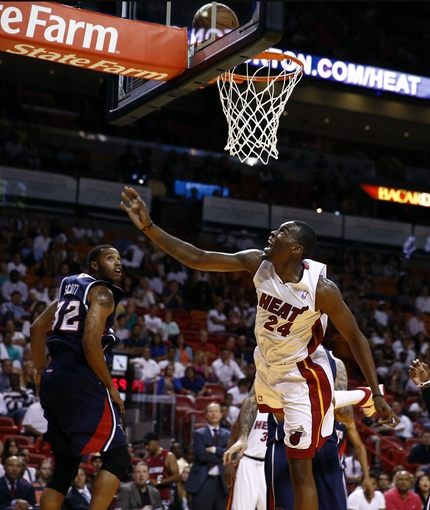 Oct 7, 2013; Miami, FL, USA; Miami Heat power forward Jarvis Varnado (24) makes a shot as Atlanta Hawks power forward Mike Scott (32) looks on in the second half at American Airlines Arena. Mandatory Credit: Robert Mayer-USA TODAY Sports