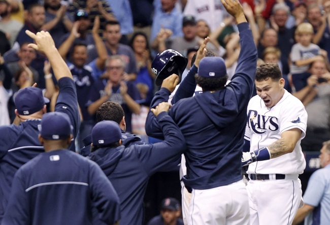 Oct 7, 2013; St. Petersburg, FL, USA; Tampa Bay Rays catcher Jose Lobaton (right) is congratulated by teammates at home plate after he hit a walk off home run during the ninth inning against the Boston Red Sox in game three of the American League divisional series at Tropicana Field. The Rays won 5-4. Mandatory Credit: Kim Klement-USA TODAY Sports