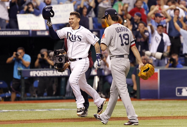 Oct 7, 2013; St. Petersburg, FL, USA; Tampa Bay Rays catcher Jose Lobaton (left) celebrates after hitting a walk off home run off of Boston Red Sox relief pitcher Koji Uehara (right) during the ninth inning of game three of the American League divisional series at Tropicana Field. The Rays won 5-4. Mandatory Credit: Kim Klement-USA TODAY Sports