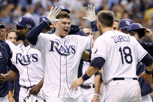 Oct 7, 2013; St. Petersburg, FL, USA; Tampa Bay Rays catcher Jose Lobaton (middle) is congratulated by teammates including Ben Zobrist (18) at home plate after he hit a walk off home run during the ninth inning against the Boston Red Sox in game three of the American League divisional series at Tropicana Field. The Rays won 5-4. Mandatory Credit: Kim Klement-USA TODAY Sports