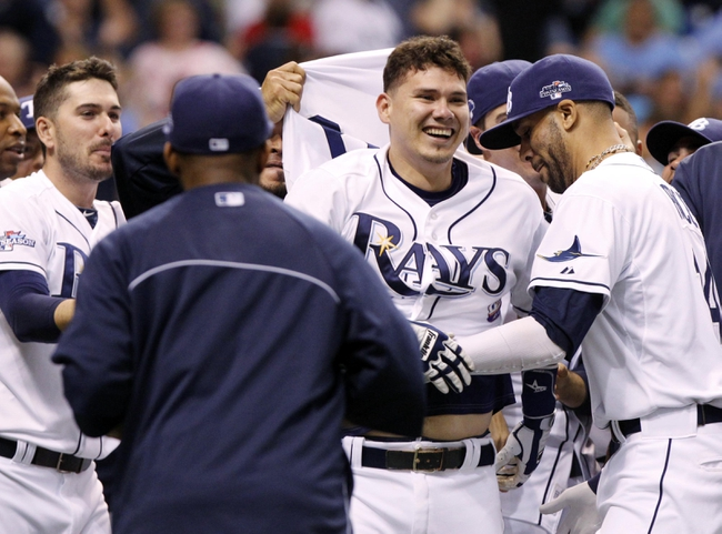 Oct 7, 2013; St. Petersburg, FL, USA; Tampa Bay Rays catcher Jose Lobaton (middle) is congratulated by teammates including David Price (right) at home plate after he hit a walk off home run during the ninth inning against the Boston Red Sox in game three of the American League divisional series at Tropicana Field. The Rays won 5-4. Mandatory Credit: Kim Klement-USA TODAY Sports