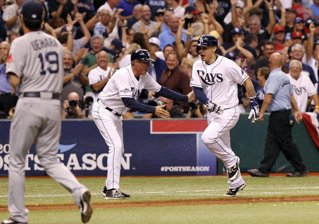 Oct 7, 2013; St. Petersburg, FL, USA; Tampa Bay Rays catcher Jose Lobaton (right) high fives third base coach Tom Foley (middle) after hitting the game-winning solo home run off of Boston Red Sox relief pitcher Koji Uehara (19) in game three of the American League divisional series at Tropicana Field. The Rays won 5-4. Mandatory Credit: Kim Klement-USA TODAY Sports