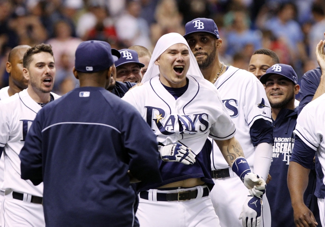 Oct 7, 2013; St. Petersburg, FL, USA; Tampa Bay Rays catcher Jose Lobaton (middle) celebrates with teammates after hitting a walk off solo home run during the ninth inning against the Boston Red Sox in game three of the American League divisional series at Tropicana Field. The Rays won 5-4. Mandatory Credit: Kim Klement-USA TODAY Sports