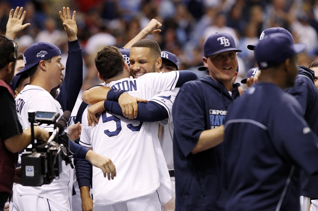 Oct 7, 2013; St. Petersburg, FL, USA; Tampa Bay Rays catcher Jose Lobaton (59) is congratulated by first baseman James Loney (middle, facing forward) after hitting a walk off home run during the ninth inning against the Boston Red Sox in game three of the American League divisional series at Tropicana Field. The Rays won 5-4. Mandatory Credit: Kim Klement-USA TODAY Sports