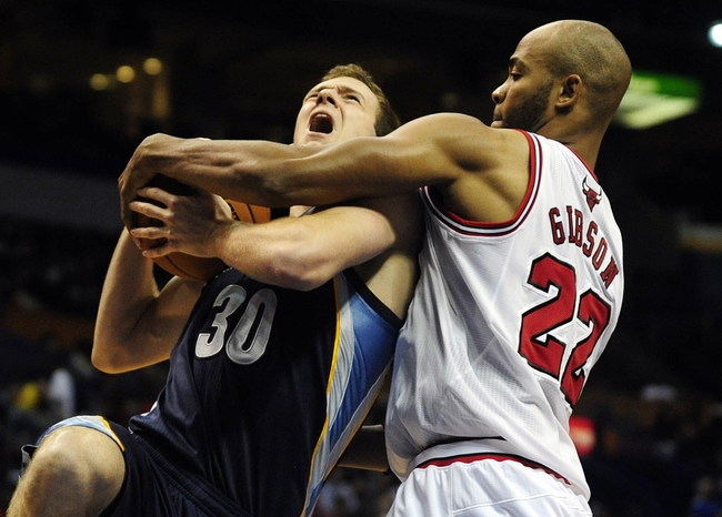 Oct 7, 2013; St. Louis, MO, USA; Memphis Grizzlies power forward Jon Leuer (30) is fouled by Chicago Bulls power forward Taj Gibson (22) during the third quarter at Scottrade Center. Chicago defeated Memphis 106-87. Mandatory Credit: Jeff Curry-USA TODAY Sports