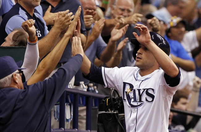 Oct 7, 2013; St. Petersburg, FL, USA; Tampa Bay Rays left fielder Sam Fuld (5) is congratulated by teammates after he scored a run during the eighth inning against the Boston Red Sox in game three of the American League divisional series at Tropicana Field. The Rays won 5-4. Mandatory Credit: Kim Klement-USA TODAY Sports