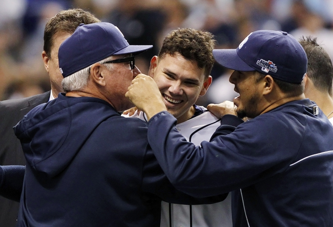 Oct 7, 2013; St. Petersburg, FL, USA; Tampa Bay Rays catcher Jose Lobaton (middle) is congratulated by manager Joe Maddon (left) and relief pitcher Joel Peralta (right)  after he hit a walk off home run during the ninth inning against the Boston Red Sox in game three of the American League divisional series at Tropicana Field. The Rays won 5-4. Mandatory Credit: Kim Klement-USA TODAY Sports