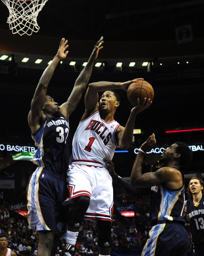 Oct 7, 2013; St. Louis, MO, USA; Chicago Bulls point guard Derrick Rose (1) goes for a lay up as Memphis Grizzlies power forward Ed Davis (32) defends during the second quarter at Scottrade Center. Chicago defeated Memphis 106-87. Mandatory Credit: Jeff Curry-USA TODAY Sports
