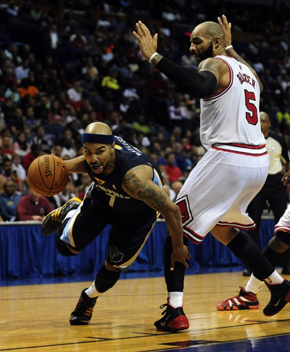 Oct 7, 2013; St. Louis, MO, USA; Memphis Grizzlies point guard Jerryd Bayless (7) handles the ball as Chicago Bulls power forward Carlos Boozer (5) defends during the third quarter at Scottrade Center. Chicago defeated Memphis 106-87. Mandatory Credit: Jeff Curry-USA TODAY Sports