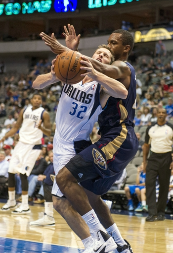 Oct 7, 2013; Dallas, TX, USA; New Orleans Pelicans small forward Lance Thomas (42) fouls Dallas Mavericks guard Mickey McConnell (32) during the second half at the American Airlines Center. The Pelicans defeated the Mavericks 94-92. Mandatory Credit: Jerome Miron-USA TODAY Sports