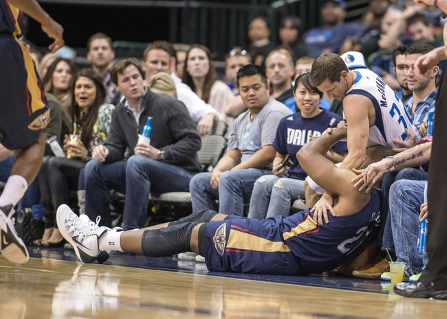 Oct 7, 2013; Dallas, TX, USA; Dallas Mavericks guard Mickey McConnell (32) and New Orleans Pelicans power forward Arinze Onuaku (21) crash into the crowd during the second half at the American Airlines Center. The Pelicans defeated the Mavericks 94-92. Mandatory Credit: Jerome Miron-USA TODAY Sports