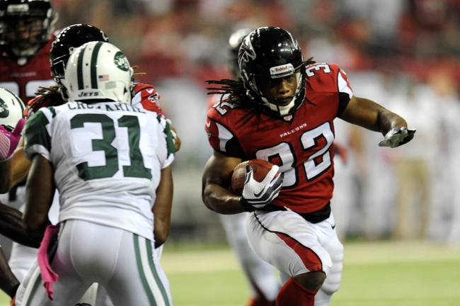 Oct 7, 2013; Atlanta, GA, USA; Atlanta Falcons running back Jacquizz Rodgers (32) runs for a touchdown past New York Jets cornerback Antonio Cromartie (31) during the second half at the Georgia Dome. The Jets defeated the Falcons 30-28. Mandatory Credit: Dale Zanine-USA TODAY Sports