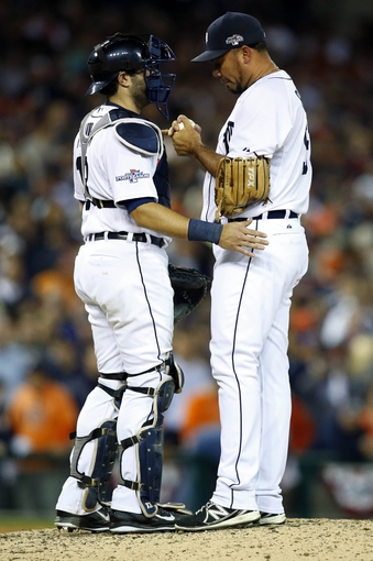 Oct 8, 2013; Detroit, MI, USA; Detroit Tigers relief pitcher Joaquin Benoit (right) talks with catcher Alex Avila (left) in the 9th inning against the Oakland Athletics in game four of the American League divisional series playoff baseball game at Comerica Park. Mandatory Credit: Rick Osentoski-USA TODAY Sports