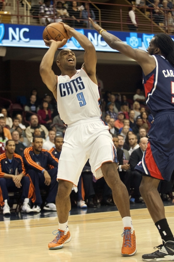 Oct 8, 2013; Asheville, NC, USA; Charlotte Bobcats shooting guard Gerald Henderson (9) looks to shoot the ball over Atlanta Hawks small forward DeMarre Carroll (5) during the first half at the U.S. Cellular Center. Mandatory Credit: Jeremy Brevard-USA TODAY Sports