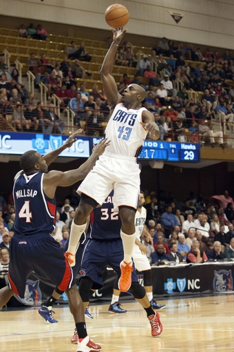 Oct 8, 2013; Asheville, NC, USA;  Charlotte Bobcats power forward Anthony Tolliver (43) goes up for a shot over Atlanta Hawks power forward Paul Millsap (4) during the first half at the U.S. Cellular Center. Mandatory Credit: Jeremy Brevard-USA TODAY Sports