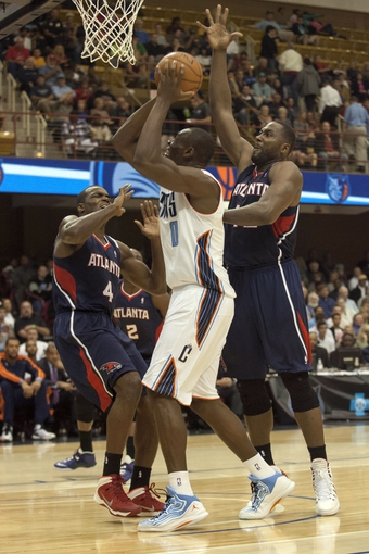 Oct 8, 2013; Asheville, NC, USA;  Charlotte Bobcats power forward Bismack Biyombo (0) tries to shoot the ball over Atlanta Hawks power forward Paul Millsap (4) during the first half at the U.S. Cellular Center. Mandatory Credit: Jeremy Brevard-USA TODAY Sports