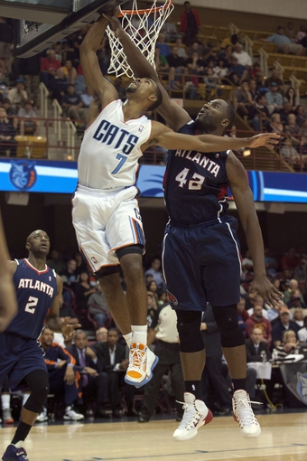 Oct 8, 2013; Asheville, NC, USA;  Charlotte Bobcats point guard Ramon Sessions (7) goes up for a shot while Atlanta Hawks power forward Elton Brand (42) defends during the first half at the U.S. Cellular Center. Mandatory Credit: Jeremy Brevard-USA TODAY Sports