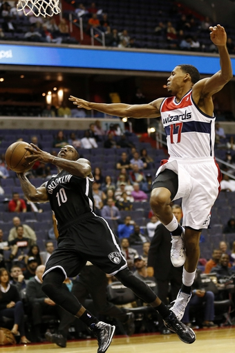 Oct 8, 2013; Washington, DC, USA; Brooklyn Nets point guard Tyshawn Taylor (10) shoots the ball as Washington Wizards shooting guard Garrett Temple (17) defends in the fourth quarter at Verizon Center. The Nets won 111-106 in overtime. Mandatory Credit: Geoff Burke-USA TODAY Sports